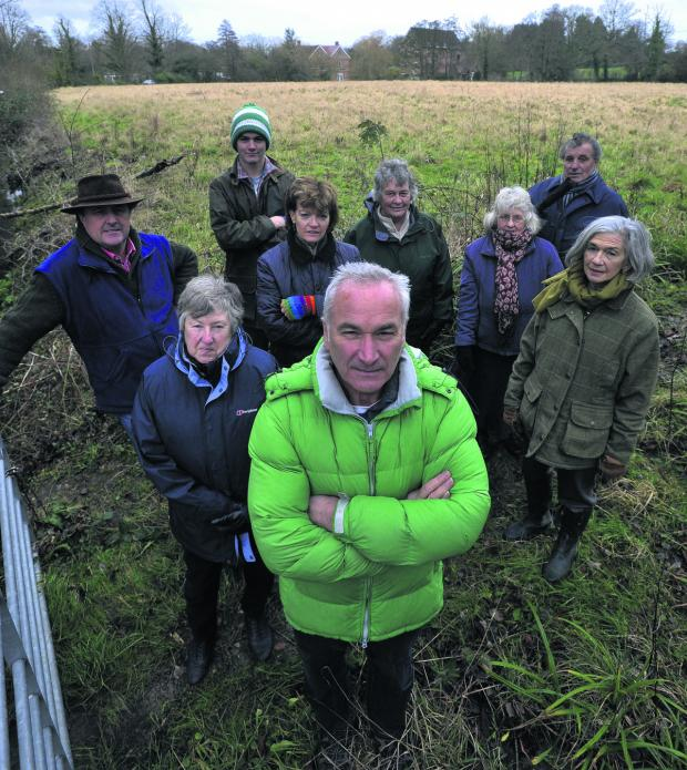 This Is Wiltshire: Mike Perry, front, with Bishopstrow villagers who are angry over support given for plans to build 35 homes on the Spurt Mead watermeadows off Boreham Road