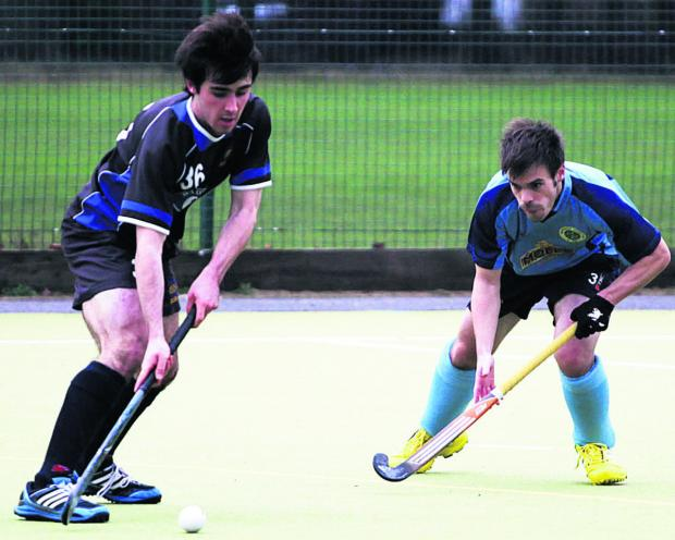 This Is Wiltshire: Devizes' Callum Lavens (black) is watched by Chris Sampson, of Chippenham, during Devizes' 3-0 win