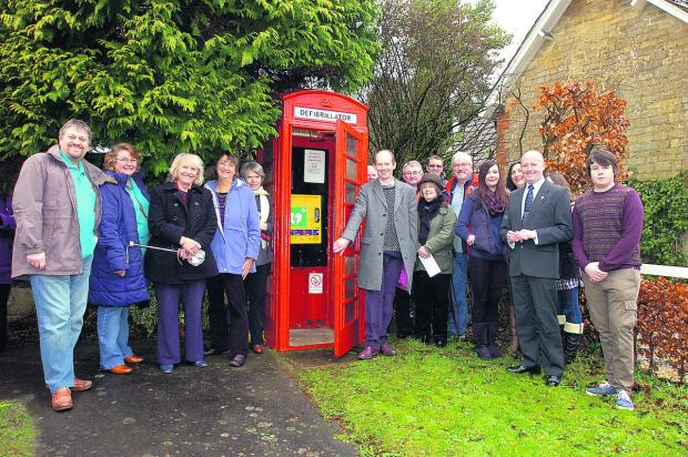 This Is Wiltshire: Dr Nick Brown opens the telephone box defibrillator as Derry Hill villagers look on