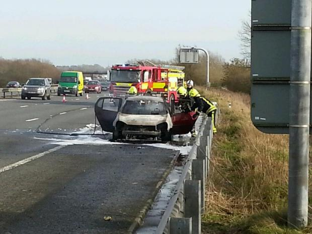 This Is Wiltshire: Firefighters extinguish remaining embers in car wreck