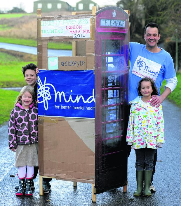 This Is Wiltshire: Sid Keyte is running the London Marathon as a telephone box for the Mind charity is pictured with his children