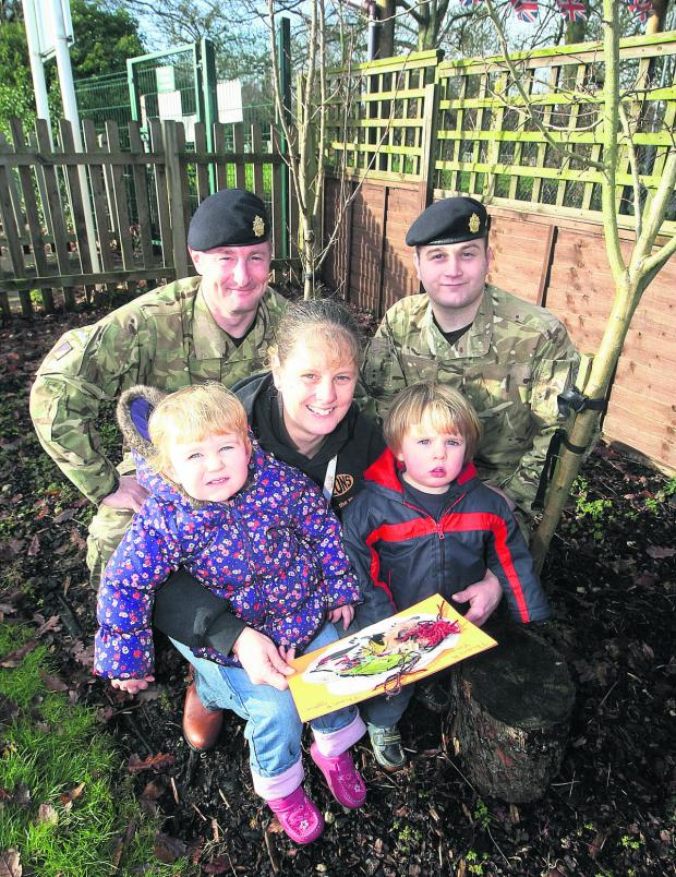 This Is Wiltshire: Cricklade Children's Centre presents a thank you card to members of the Army who helped clear the centre's garden. Sgt John Bennett and Private Matthew Hughes with play worker Liz Baker and children Penny Hutchings and Oliver Green