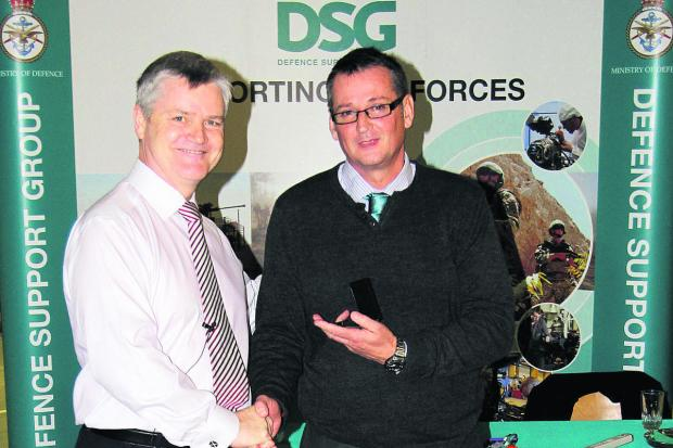 This Is Wiltshire: Phil Hawkins, right, is presented with his medal by Defence Support Group chief  executive, Archie Hughes
