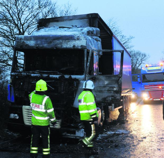 This Is Wiltshire: Fire officers look at the damaged lorry cab that caught fire at the lay-by near Seend fork this morning