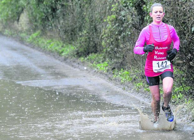 This Is Wiltshire: Leading lady Claire Frances, from Yatton Keynell, who was 44th overall splashes her way towards the finishing line,