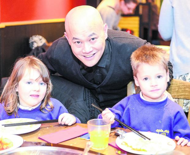 This Is Wiltshire: Children from Oakhurst Primary School celebrate the Chinese New Year at Oriental Aroma, in Royal Wootton Bassett. From left, Evie, owner James Huynh and Sebastian. Picture: Alex Skennerton