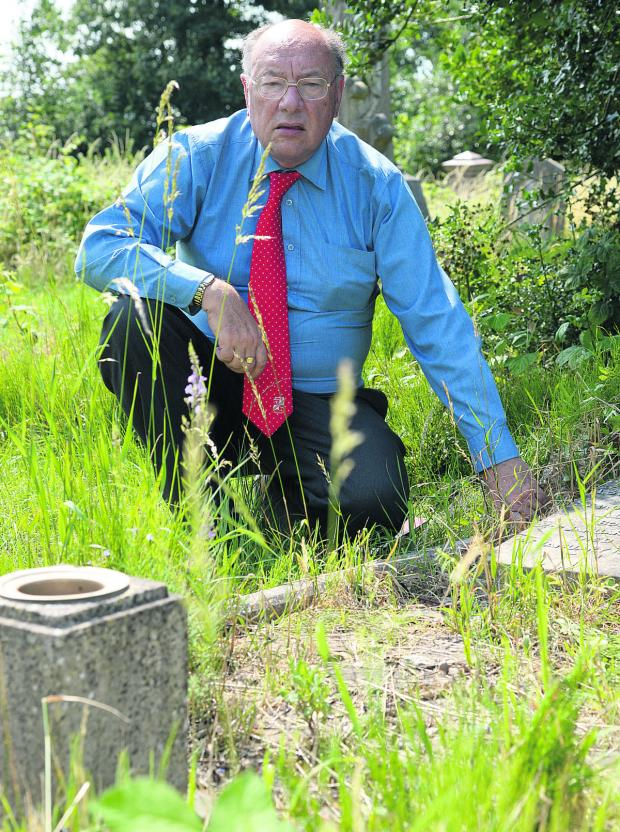 This Is Wiltshire: Historian Dick Mattick in Radnor Street Cemetery at the grave of STFC player Sam Allen