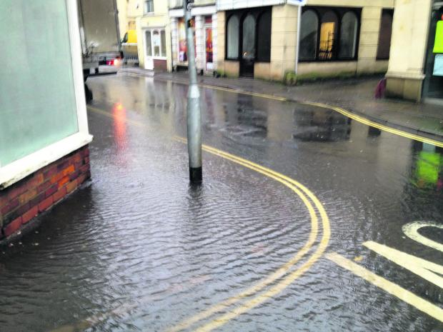 This Is Wiltshire: Water overflows from a blocked drain at the corner of Duke Street and Church Street, Trowbridge, today