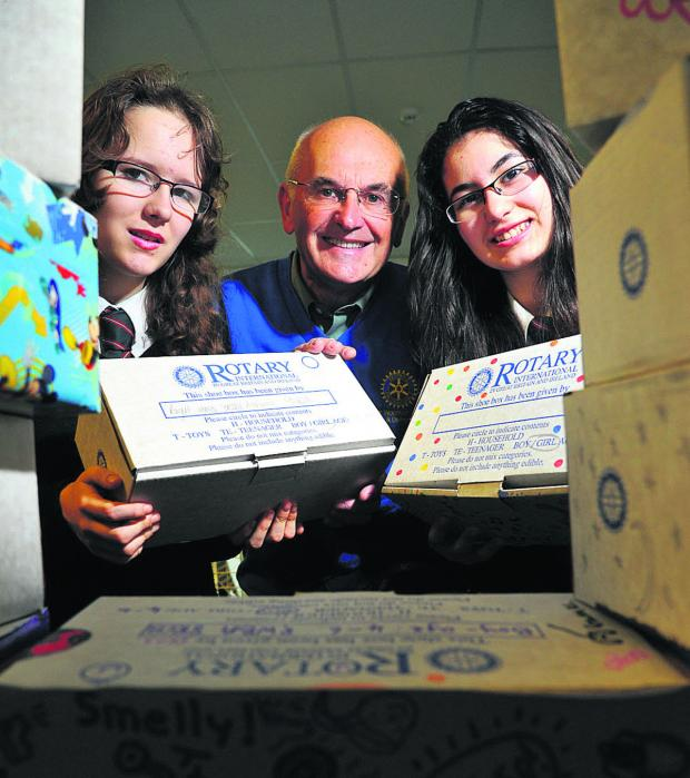 This Is Wiltshire: Students at Wootton Bassett Academy have been filling and decorating shoeboxes to send to children in Eastern Europe. Pictured, left to right, are Ellie, John Coran of Wotton Bassett Rotary Club and Veronica