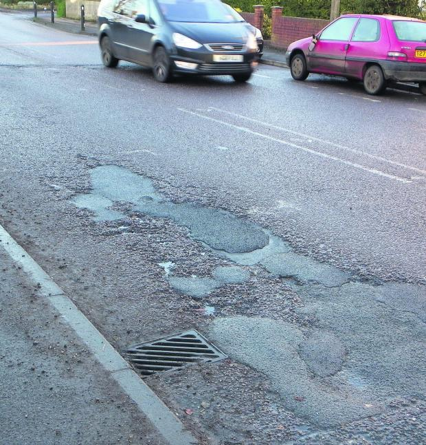 This Is Wiltshire: Potholes, like these in Bath Road, Devizes, are being repaired but town councillors fear that the work may not last