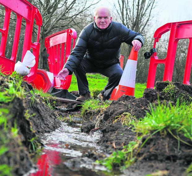 This Is Wiltshire: Before maintenance on the Liden Drive footpath, residents including John McClay got out their shovels to dig a trench to chanel away floodwater. Residents say the issue has still not been resolved