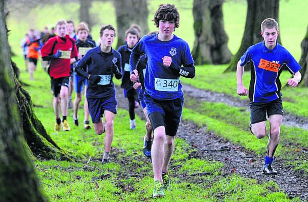 This Is Wiltshire: Junior boys competitiors make their way through an avenue of trees at Grittleton House School on Saturday