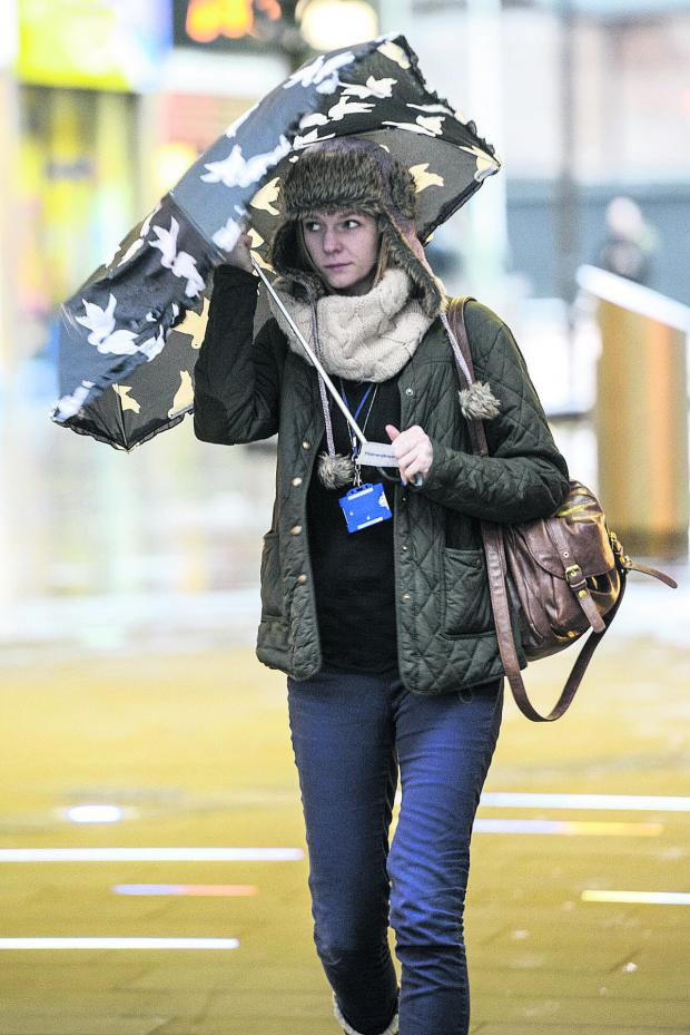 This Is Wiltshire: A shopper braves the wet and windy weather in Swindon Town Centre