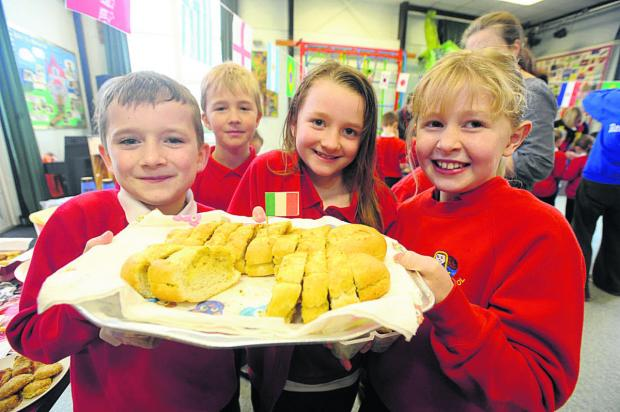 This Is Wiltshire: Redland pupils, from left, Charlie, Chloe and Emily serve up a platter of garlic bread as part of the Italian cuisine