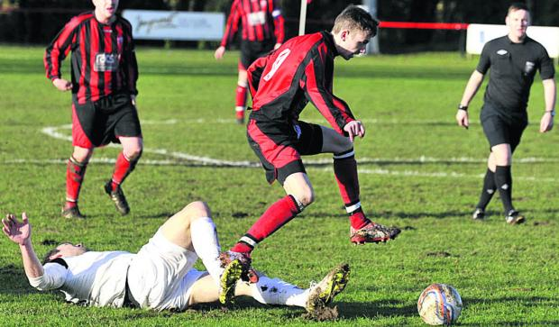 This Is Wiltshire: Warminster Town's Jack Miluk avoids a sliding tackle from Roman Glass defender Nat Abrahams