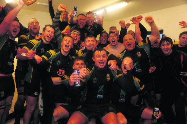 This Is Wiltshire: Trowbridge's players start the celebrations in the sanctuary of their changing room after their Southern Counties Intermediate Cup final victory over Bletchley at Doric Park in foul weather conditions on Saturday