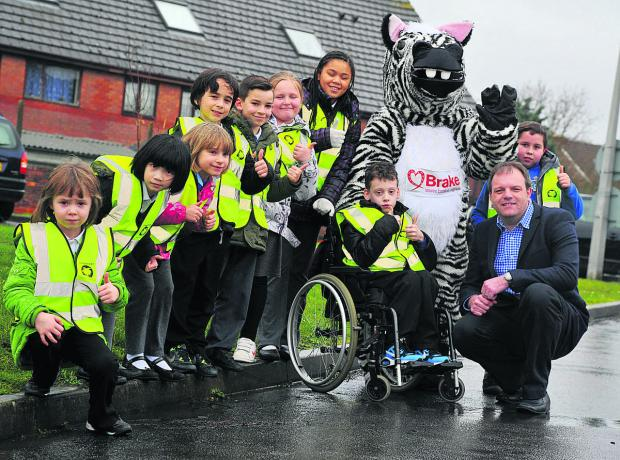 This Is Wiltshire: Zak The Zebra,  the mascot of road saftey charity Brakevisiting children at Robert Le Kyng School. From left,  Alex Theobald as  Zac and Dominic Threlfall from Pebley Beach