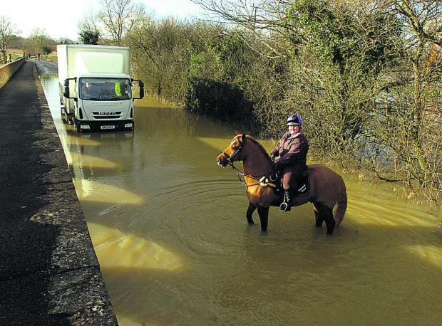This Is Wiltshire: Rider Rebekah Read and her horse cope with floods at Langley Burrell, near Chippenham, today
