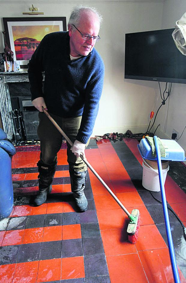 This Is Wiltshire: Brian Warneford pushes the flood water out of his home