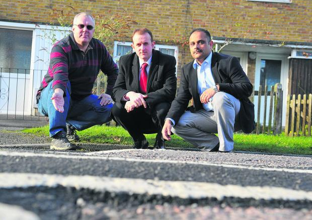 This Is Wiltshire: Resident Glenn Stanley, right, Labour group deputy leader Mark Dempsey, left, and Walcot councillor Abdul Amin inspecting the damage to the road in Kingswood Avenue