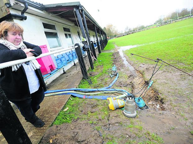 This Is Wiltshire: Julie Exton, of Malmesbury Vics FC, watches water being pumped off the pi