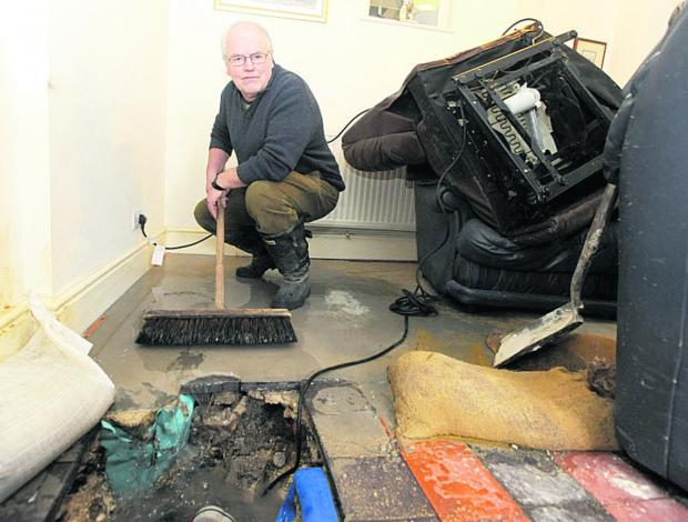 This Is Wiltshire: Brian Warneford surveys the flood damage in his home in West Street, Aldbourne