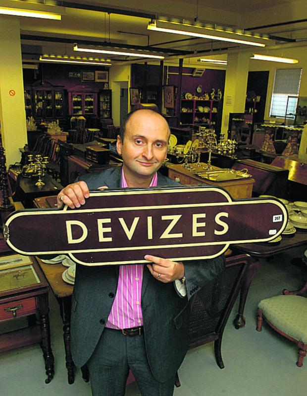 This Is Wiltshire: Andrew Aldridge with the Devizes station sign which is going under the hammer on Saturday