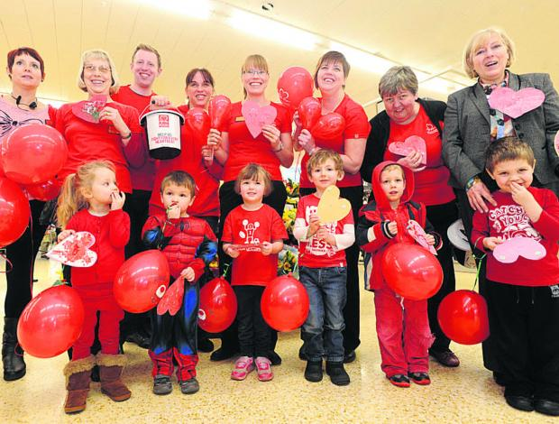 This Is Wiltshire: Chippenham Sainsbury's staff and children from the Busy Bees Nursery dress up to support the BHF on Valentine's Day. Back, Molly Randell, Lesley Hern, Greg Rochester, of Sainsburys, Claire Fern, Sam Hey, Amanda Houston, Lyn Gardener and Wendy Massingham
