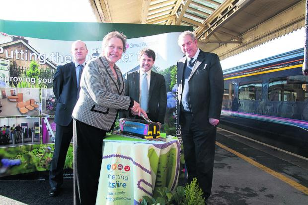 This Is Wiltshire: Baroness Kramer cuts a cake at Chippenham train station to officially launch the Transwilts service with, from left, Matthew Golton, project and planning director with First Great Western, Chippenham MP Duncan Hames and John Thomson, deputy leader of Wilt
