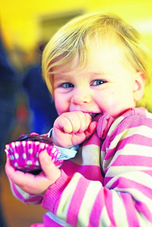 This Is Wiltshire: Amelia tucking into the cakes on offer at the