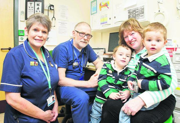 This Is Wiltshire: From left, SEQOL nurse Anita Fisher and Bob Sanderson, director of unscheduled care at Carfax Health Enterprise, with Sharon Gerry and her two grandchildren, Eli, two, and Zachery, three