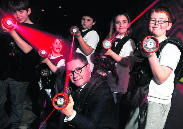 This Is Wiltshire: Robert Buckland MP tries out a bit of combat at Lazerquest with, from left, Andrew, Lexie, Harry, Jodie and Joshua. Picture: DAVE COX