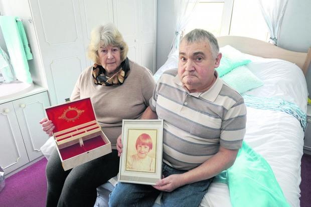 This Is Wiltshire: Anne and Peter Sinfield, from Brandenstoke, whose home was broken into. Anne is holding her empty jewellery box and Peter a picture of their daughter Karen, who died of cancer aged eight