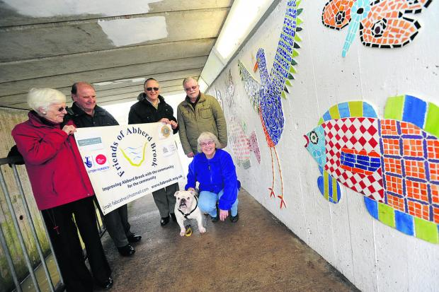 This Is Wiltshire: Morag and Andy Baulf, left, Francis Bosworth, David Beesby, Glenda Beesby and Hamilton the dog with the mosaic