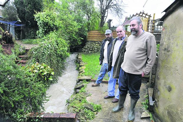 This Is Wiltshire: From left, Andy Hinton, Ken Oliver and Andy Beswick keep an eye on the rising stream which runs between their homes                         Photo: Glenn Phillips