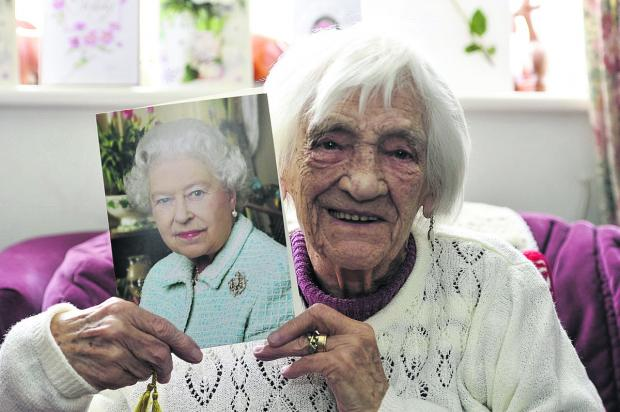 This Is Wiltshire: Doris Wilcox celebrates her 100th birthday holding her special card from the Queen.  Picture: Alex Skennerton