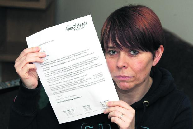 This Is Wiltshire: Mum of nine Michelle Martin with the letter she received from Abbey Meads Medical Practice