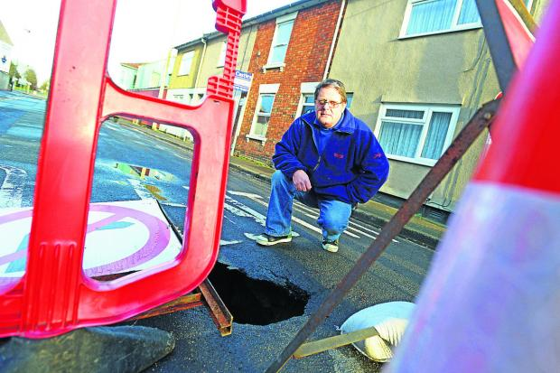 This Is Wiltshire: A sinkhole has opened  up along Linslade Road, Rodbourne. Pictured is Robert Gosling of Ron's Stores who feels it has affected his business