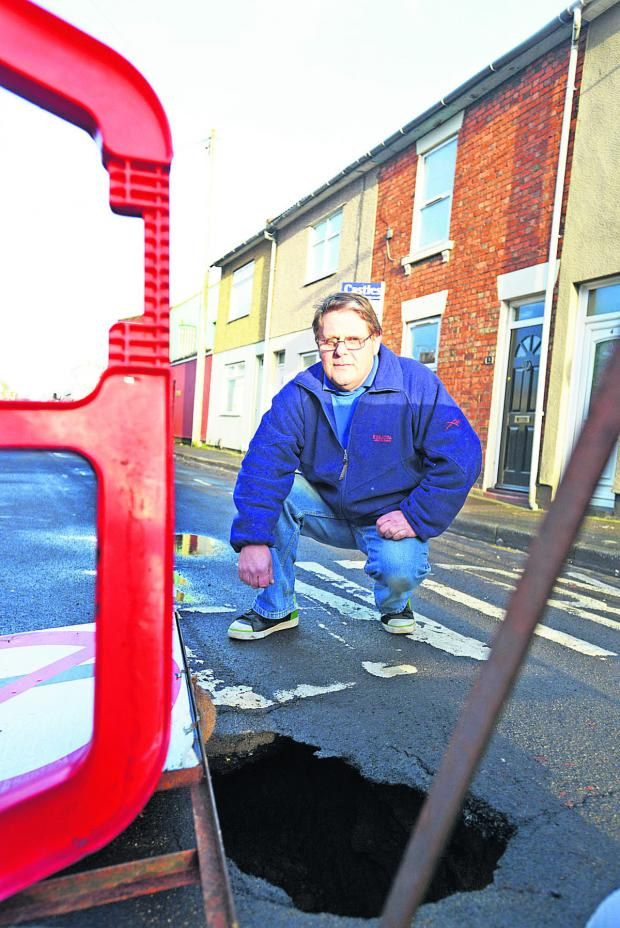 This Is Wiltshire: Robert Goslin, of Ron's Stores, with the hole at Linslade Road, Rodbourne