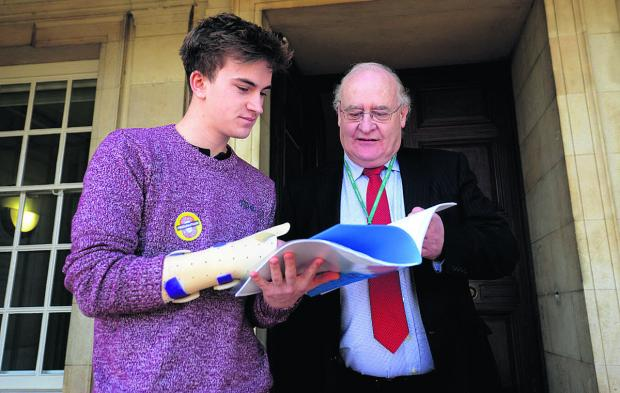 This Is Wiltshire: Chris Baker, a volunteer at Salisbury's Grosvenor House youth centre hands a petition to Coun Richard Gamble