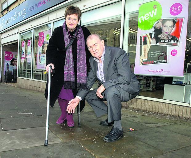 This Is Wiltshire: Coun Bill Douglas and Coun Mary Fallon inspect the area of pavement where the pensioner fell