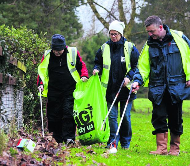 This Is Wiltshire: Scott Jacobs-Lange, Sovereign Housing Association's community investment coordinator, right, litter-picking with Green Square staff as the Charter Road estate in Chippenham gets a spring clean