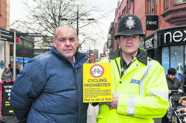 This Is Wiltshire: Anti-social behaviour investigator Jerry Law and Community Beat Manager PC Paul Bezzant  with the additional signs  being  put up in the town centre telling people not to cycle there