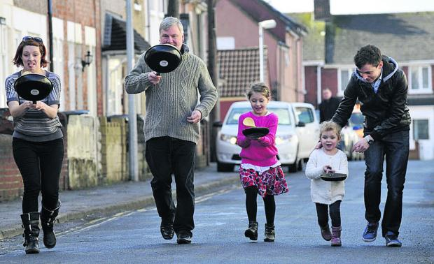 This Is Wiltshire: Rev Harvey Gibbons, second right, says pancake races at St Augustine's Church, Rodbourne, are part of new plans to boost the congregation