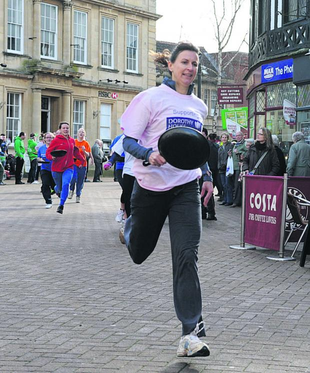 This Is Wiltshire: Dorothy House Hospice Care nurse Claire Michell wins the ladies' pancake race in Fore Street, Trowbridge, today