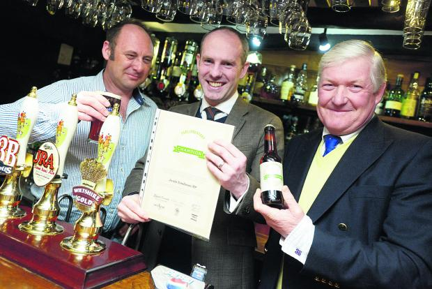 This Is Wiltshire: MP Justin Tomlinson, centre, being presented with an award for his work in abolishing the beer duty escalator from landlord Steve Snook, left, and James Arkell