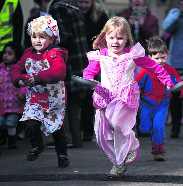 This Is Wiltshire: Lola, centre, and friends take part in the pancake races in Chippenham