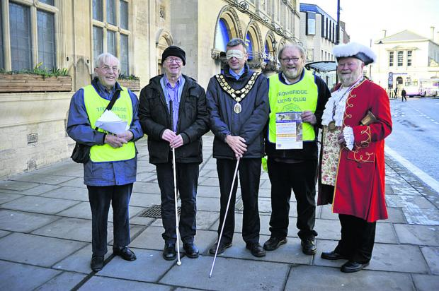 This Is Wiltshire: Trowbridge mayor David Halik walked through the town centre blindfolded and partly guided by members of Trowbridge Lions Club and town crier Trevor Heeks
