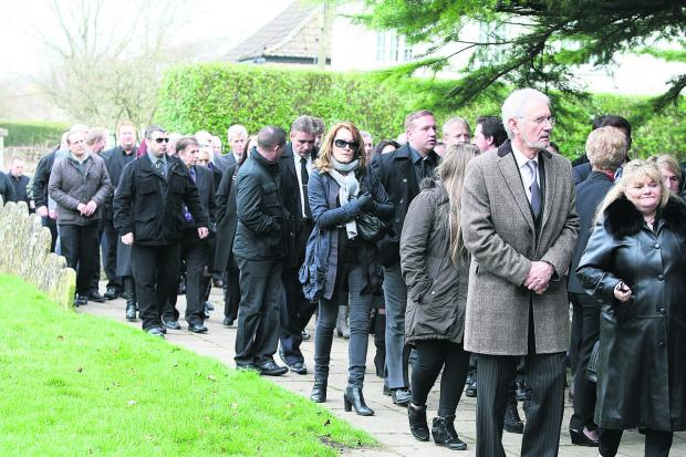 This Is Wiltshire: Mourners gather at Cricklade's St Sampson's church for the funeral of Patrick Austen