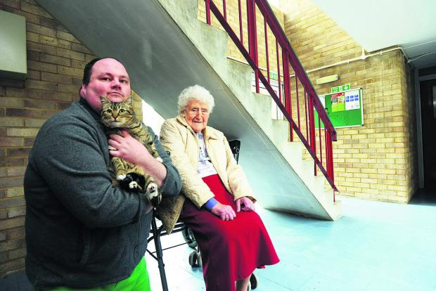 This Is Wiltshire: Doris Turner in the space under the stairs where she keeps her wheelchair, which is now deemed to be a fire risk. With her is Philip Dunn with his cat Sally. He has also been told he cannot keep the animal because she is a fire risk